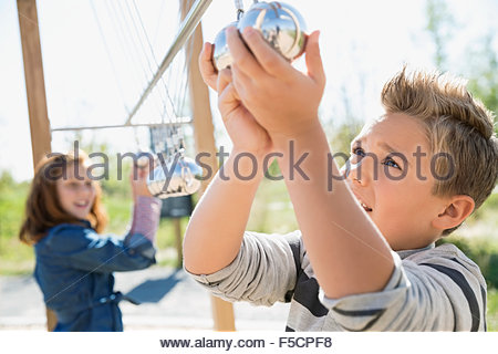 Curious boy playing with large Newton's Cradle playground - Stock Photo