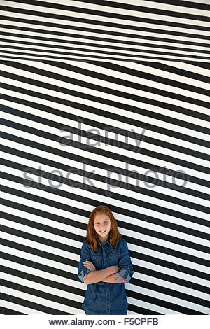 Portrait girl against black and white striped wall - Stock Photo