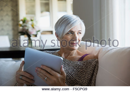Pensive woman using digital tablet on sofa - Stock Photo
