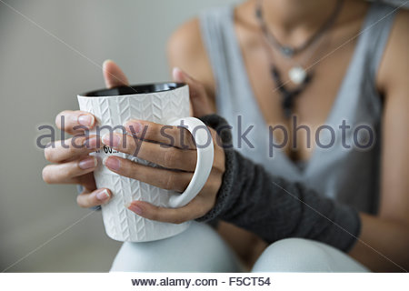 Close up young woman drinking coffee wrist warmers - Stock Photo