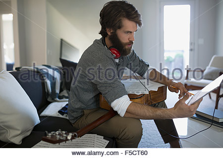 Man with guitar recording music with digital tablet - Stock Photo