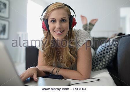 Portrait smiling woman with headphones using laptop sofa - Stock Photo