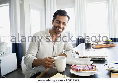 Portrait smiling man drinking coffee and reading newspaper - Stock Photo