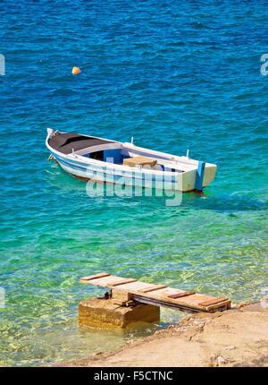 Old wooden fishermen boat on turquoise beach, Mediterranean sea - Stock Photo