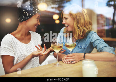 Two attractive women enjoying a glass of white wine together in a pub sitting at a table laughing and chatting with - Stock Photo