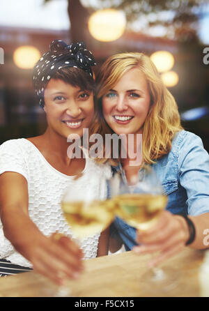 Fun attractive young female friends celebrating with white wine clinking their glasses in a toast as they smile - Stock Photo