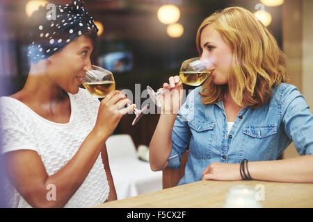 Two attractive young women meeting up in a pub for a glass of white wine sitting at a counter smiling at each other - Stock Photo
