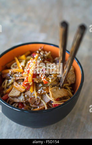 Stir fry with vegetables and meat garnished with sesame seeds in bowl with chopsticks. Traditional asian cuisine - Stock Photo