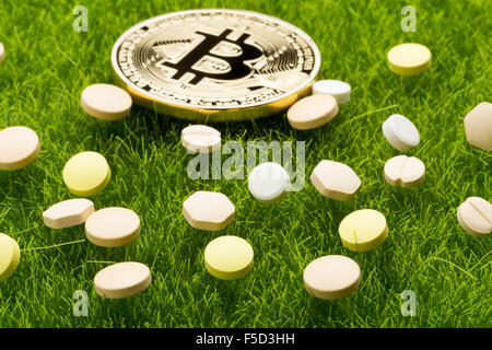 Different pills and bitcoin coins on the grass background - healthcare cost concept - Stock Photo