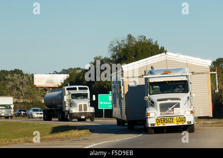 Moving home - shiny American Volvo truck transporting mobile home wide load on trucking route Interstate 10, Louisiana, - Stock Photo