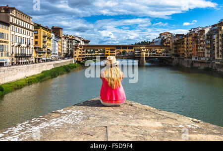 A young woman enjoying the view of the Ponte Vecchio and the Arno River, Florence, Tuscany, Italy. - Stock Photo