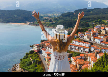 A beautiful young woman admiring the Lastres view from San Roque Viewpoint, Concejo de Colunga, Asturias, Spain. - Stock Photo