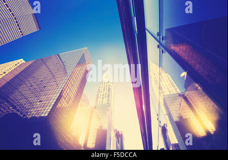 Vintage style Manhattan skyscrapers at sunset reflected in windows, NYC, USA. - Stock Photo