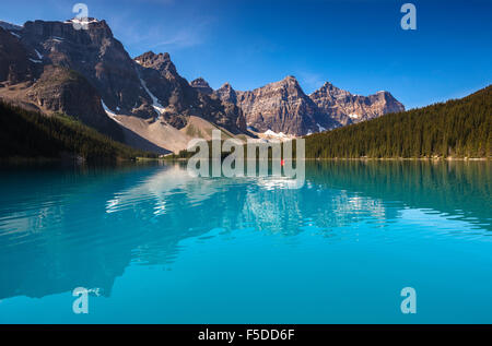 A red canoe in the beautiful Moraine Lake, in Banff National Park, Alberta Canada (Canadian Rocky Mountains). - Stock Photo