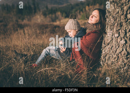 Mother and son sitting under the tree. - Stock Photo