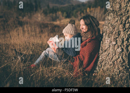 Mother and son in nature. Reading book and smiling. - Stock Photo
