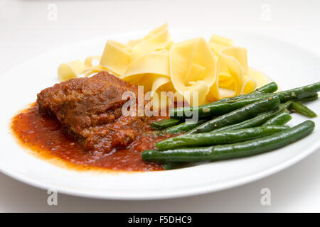 Veal cheeks with noodles and beans - Stock Photo