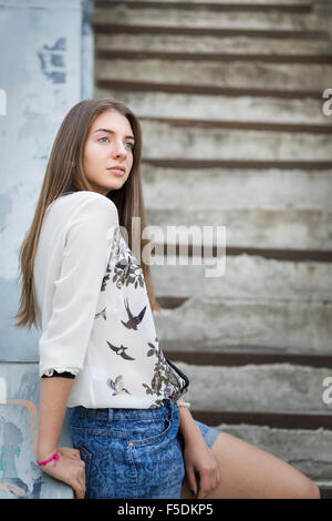 Young caucasian hipster girl relaxing on stairs in the city. - Stock Photo