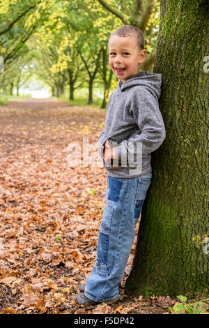 Smiling 6 year old boy leaning on a tree - Stock Photo