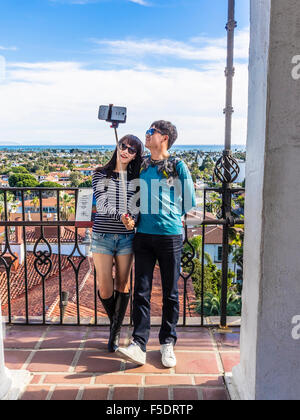 A young adult Chinese couple take a selfie using a selfie stick on top of the Santa Barbara County Courthouse in - Stock Photo