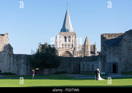 Wedding couple being photographed in grounds of Rochester Castle, Rochester, Kent, England, United Kingdom - Stock Photo