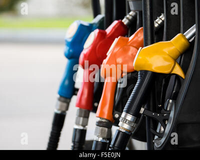 Four different fuel nozzles in gas station - Stock Photo
