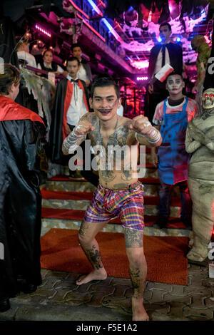 Tattooed Shirtless Thai man and Halloween attired staff at a bar venue In Walking Street Pattaya Thailand - Stock Photo
