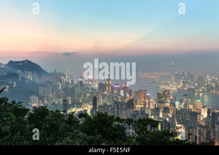 Hong Kong skyline shot after sunset from the top of a mountain in Hong Kong island. The view goes through the Victoria harbor un