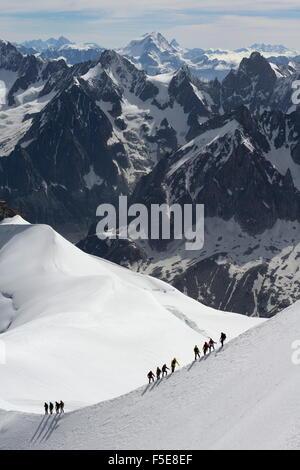 Mountaineers and climbers hiking on a snowy ridge, Aiguille du Midi, Mont Blanc Massif, Chamonix, Haute Savoie, - Stock Photo