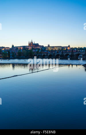 View of Charles Bridge, the Castle District and St. Vitus's Cathedral across the Vltava River at sunset, Prague, - Stock Photo