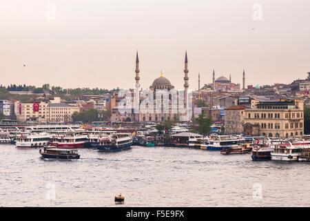 New Mosque (Yeni Cami) with Hagia Sophia (Aya Sofya) behind seen across the Golden Horn, Istanbul, Turkey, Europe - Stock Photo