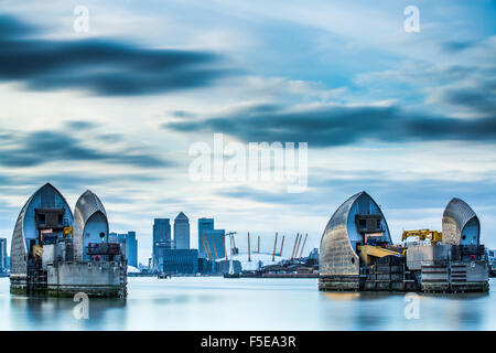 Thames Barrier on River Thames and Canary Wharf in the background, London, England, United Kingdom, Europe - Stock Photo