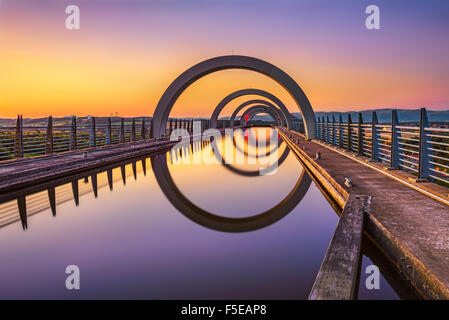 Falkirk Wheel at sunset. Falkirk Wheel is a rotating boat lift in Scotland and connects the Forth and Clyde Canal - Stock Photo