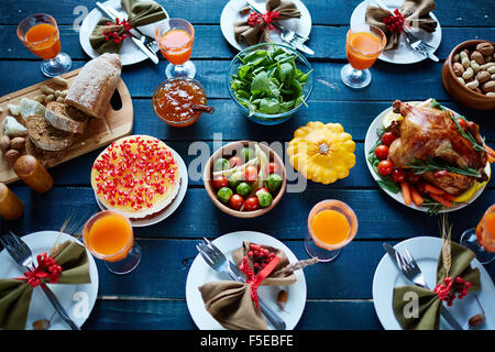 Roasted turkey, glasses with juice, vegetables, nuts, dessert, fresh bread and tableware on dinner table - Stock Photo