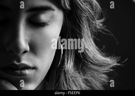 Portrait of young woman with her eyes closed - Stock Photo