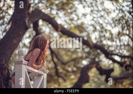 Girl leaning against wooden fence in backyard - Stock Photo