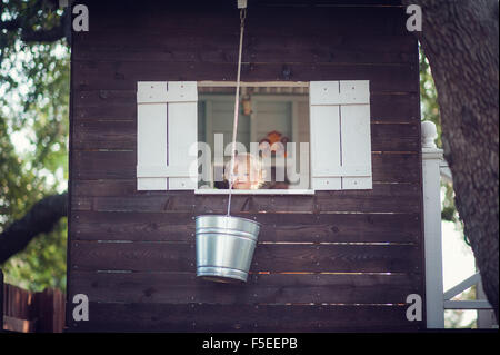 Boy in tree house looking out of the window - Stock Photo