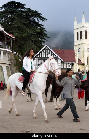 India, Himachal Pradesh, Shimla (Simla), The Ridge Scandal Point, woman riding white horse outside Christ Church - Stock Photo