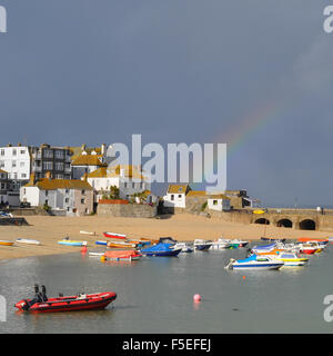 St Ives rainbow - a beautiful rainbow over brightly coloured fishing boats in the picturesque english seaside beach - Stock Photo