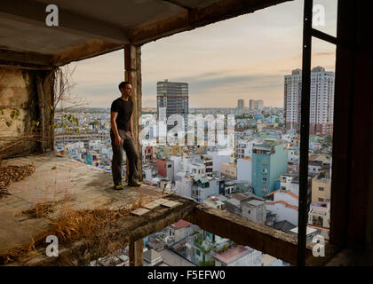 Man standing in derelict building looking at city, Ho Chi Minh, Vietnam - Stock Photo