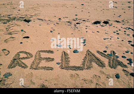 Relax written in sand on the beach - Stock Photo