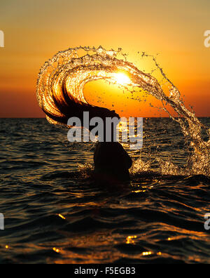 Silhouette of woman in sea throwing her head back - Stock Photo