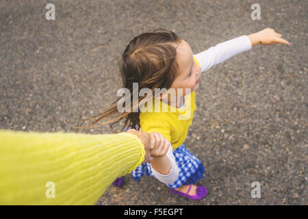 Overhead view of a girl holding her mother's hand - Stock Photo