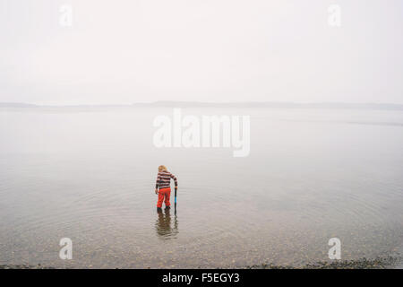 Boy standing in shallow water in a lake - Stock Photo