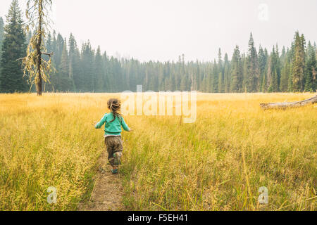 Rear view of girl running down a track in the countryside - Stock Photo