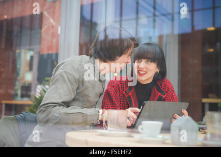 Couple of young beautiful caucasian man and woman business colleague seated on a bar using tablet and smartphone - Stock Photo