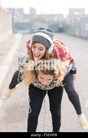 Knee figure of two young curly and straight blonde hair caucasian woman listening music with headphones, one holding - Stock Photo