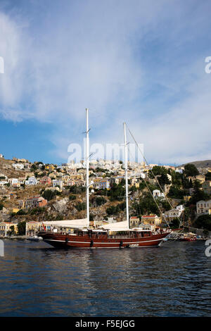 A Gulet anchored in Yialos bay on the Greek island of Symi. - Stock Photo