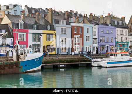 Colourful picturesque terraced houses alongside Weymouth's inner harbour - Stock Photo