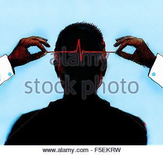 Hands holding pulse trace inside of man's head - Stock Photo